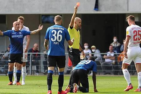 Schiedsrichter Franz Boskop (M) zeigt Paderborns Jamilu Collins (2.v.r/unten) die Gelb-Rote Karte. Foto: Friso Gentsch/dpa