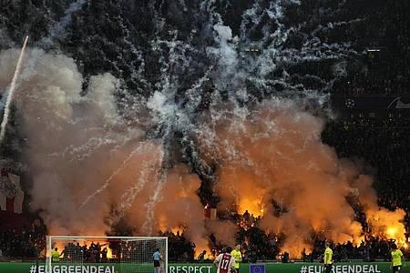 Feuer und Rauch:Ajax-Fans zünden Feuerwerk während des Spiels. Foto: Peter Dejong/AP/dpa