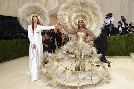 Harris Reed (l) und Iman: Ihr Kleid mit riesigem Hut solle «ein Licht nach all dieser Dunkelheit» symbolisieren, sagte das Model. Foto: Evan Agostini/Invision via AP/dpa