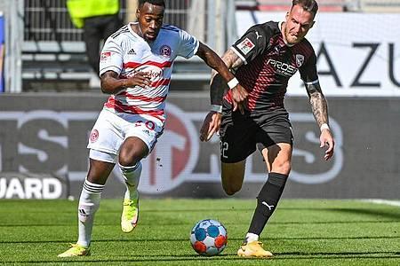 Khaled Narey von Düsseldorf (l) und Patrick Schmidt vom FC Ingolstadt jagen dem Ball hinterher. Foto: Armin Weigel/dpa