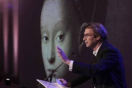 """Taco Dibbits, Generaldirektor des Rijksmuseums, spricht über die Ausstellung """"Remember Me"""" (dt:Vergiss mich nicht), während das Porträt einer jungen Frau von Petrus Christus auf die Leinwand projiziert wird. Foto: Peter Dejong/AP/dpa"""