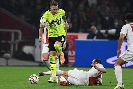 Vom Ball getrennt: Daley Blind (unten) und BVB-Kapitän Marco Reus. Foto: Bernd Thissen/dpa