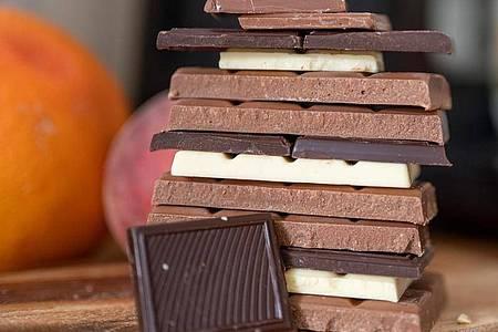 Stücke von Vollmilchschokolade, weißer Schokolade und Zartbitterschokolade liegen auf einem Holzbrett. Foto: Monika Skolimowska/dpa-Zentralbild/dpa