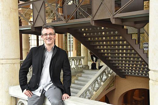 Mann steht unter einer Treppe
