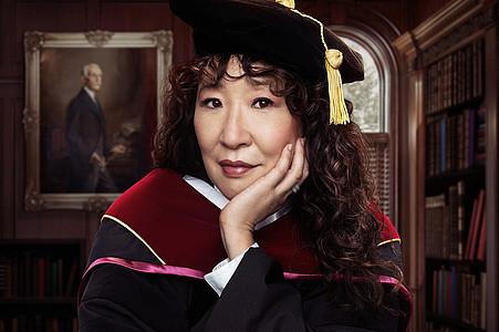 Die Professorin sitzt in ihrem klassischen Outfit an einem Pult und schaut in die Kamera.