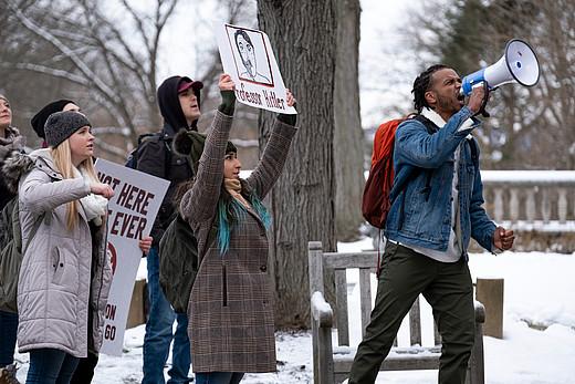 Studierende stehen auf dem Uni Campus und protestieren mit Plakaten.