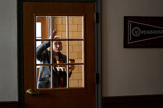 Eine ältere Dozentin steht mit einem Kaffee vor einer Glastür und gestikuliert aufgeregt.