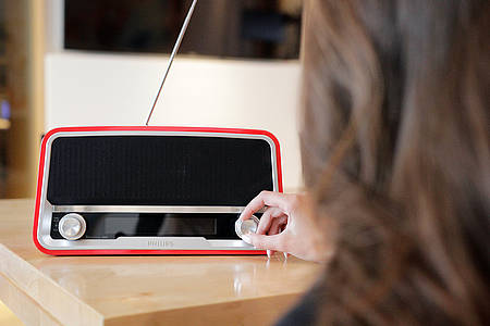 Frau dreht am Empfang eines UKW Radios