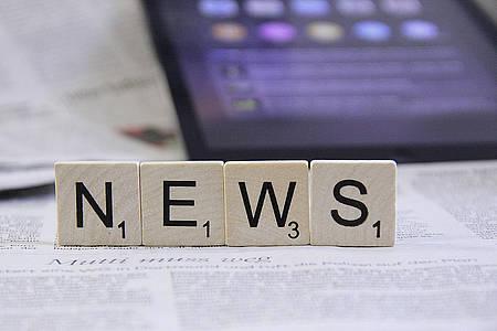 """""""News"""" geschrieben in Scrabble-Buchstaben, die vor einem Tablet stehen"""