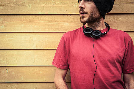 Mann im roten Shirt mit Kopfhörern um den Hals