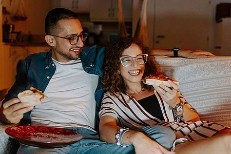 Mann und Frau sitzen auf dem Sofa und schauen Serie