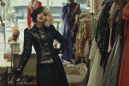Cruella-Darstellerin Emma Stone vor einer Kleiderstange