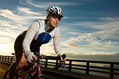 Frau fährt mit dem Rennrad über eine Brücke