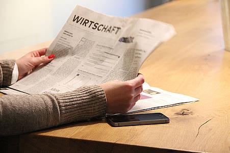 Frau liest Wirtschaftsteil einer Zeitung