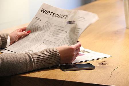 Frau liest den Wirtschaftsteil einer Zeitung