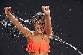 Mädchen bekommt Wasser ins Gesicht gespritzt und freut sich